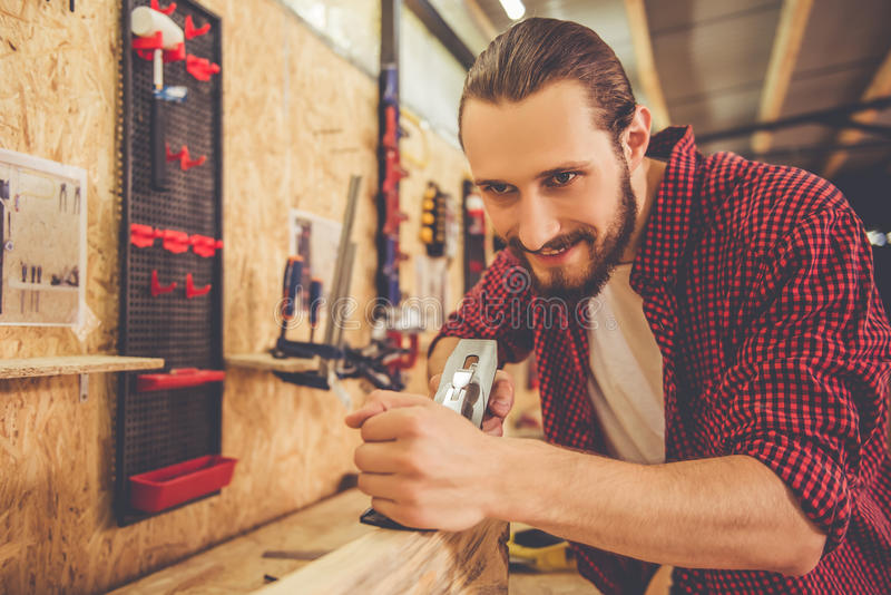 Handsome carpenter working. Handsome carpenter is smiling while working with wood and carpenter's plane in the workshop stock image