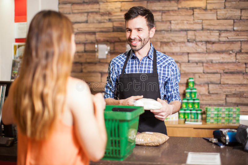 Handsome cashier enjoying his work. Cashier and customer smiling face to face while buying groceries at a supermarket royalty free stock photography