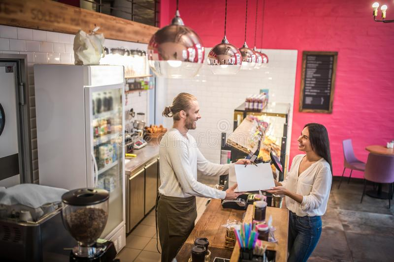 Handsome cashier giving bag with order to pleasant beautiful customer stock images