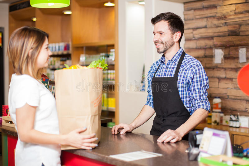 Handsome cashier helping out a customer. Profile view of a young male cashier helping a customer pay for all her groceries at a store stock image