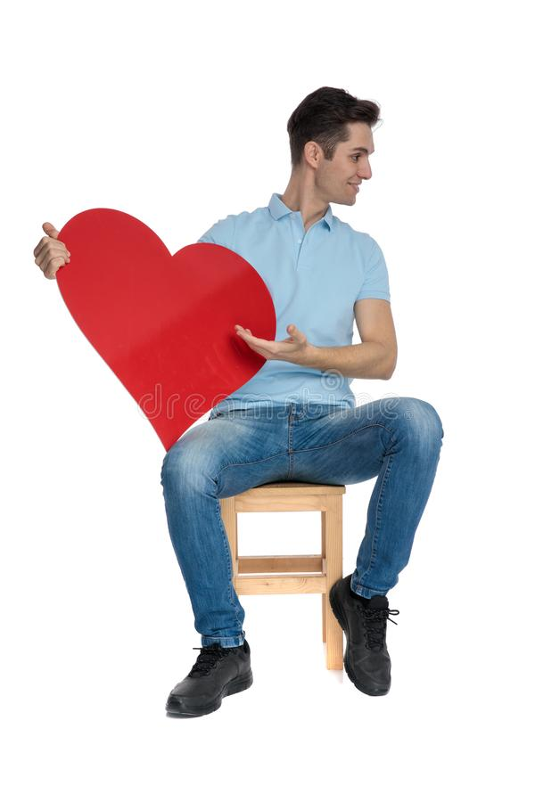 Handsome casual guy presenting a red heart shape. To the side and smiling while wearing blue jeans and sitting on a chair on white studio background royalty free stock images