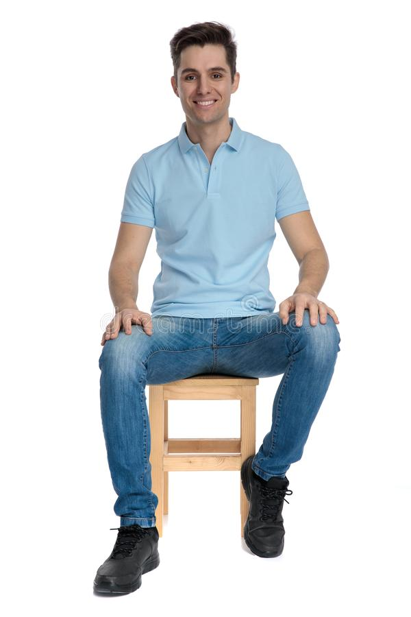 Handsome casual guy wearing a blue shirt and jeans. Posing and sitting on a chair on white studio background stock image