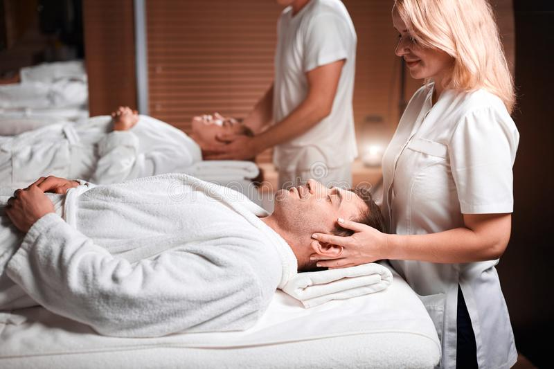 Man receiving back massage from masseur in spa royalty free stock images
