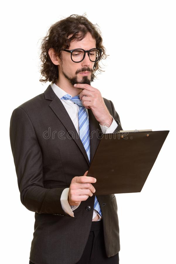 Handsome Caucasian businessman reading clipboard while thinking royalty free stock image