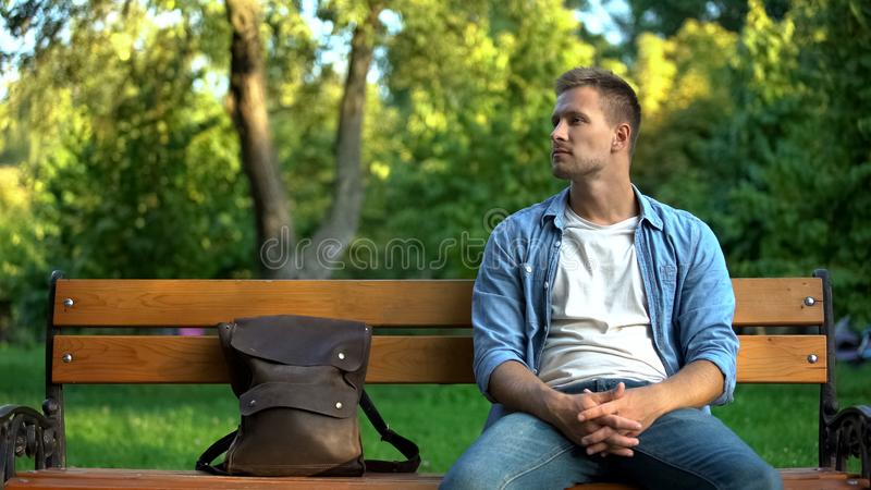 Handsome caucasian male sitting park bench with backpack, urban recreation stock photography