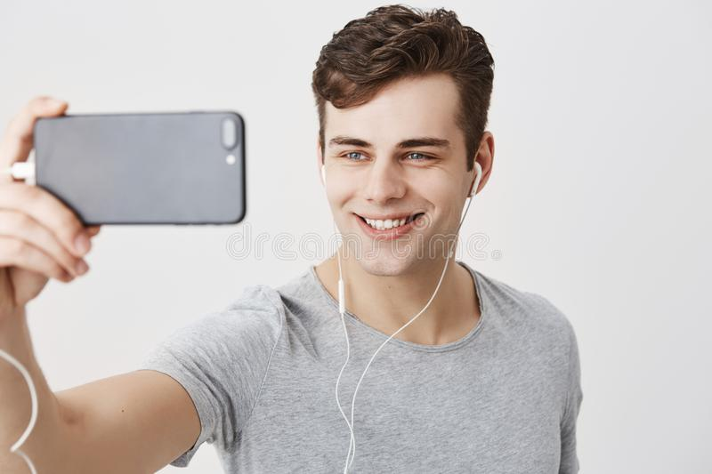 Handsome caucasian young male with dark hair and appealing blue eyes holding mobile phone, posing for selfie, looking at. Camera with flirty smile. Good-looking royalty free stock image