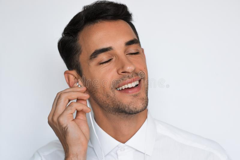 Handsome caucasian young man enjoying his favorite music. Happy stylish smiling man in headphones against gray background. stock photo