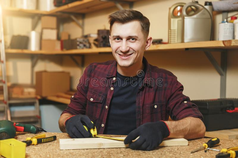 Handsome smiling young man working in carpentry workshop at wooden table place with piece of wood stock photo