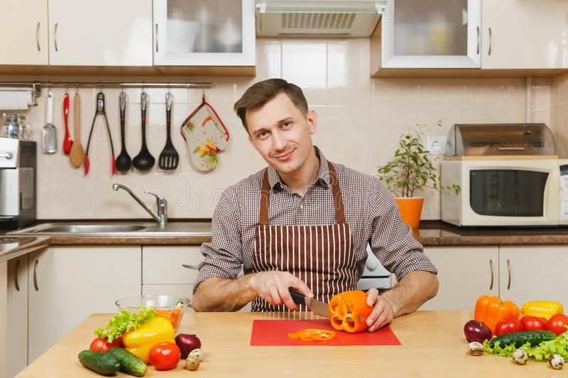 Handsome caucasian young man, sitting at table. Healthy lifestyle. Cooking at home. Prepare food. royalty free stock image