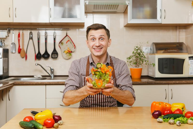 Handsome caucasian young man, sitting at table. Healthy lifestyle. Cooking at home. Prepare food. Handsome fun caucasian young man in apron, brown shirt sitting stock photos