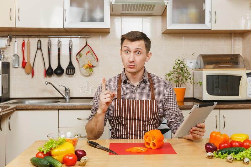 Handsome caucasian young man, sitting at table. Healthy lifestyle. Cooking at home. Prepare food. royalty free stock photo