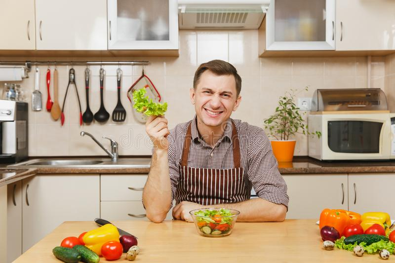 Handsome caucasian young man, sitting at table. Healthy lifestyle. Cooking at home. Prepare food. stock images