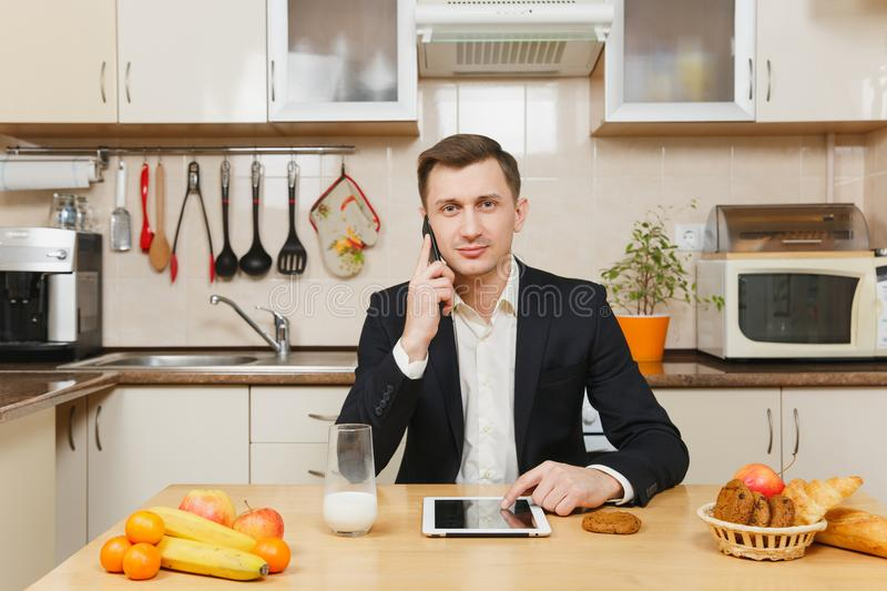Handsome caucasian young man, sitting at table. Healthy lifestyle. Cooking at home. Prepare food. royalty free stock photos