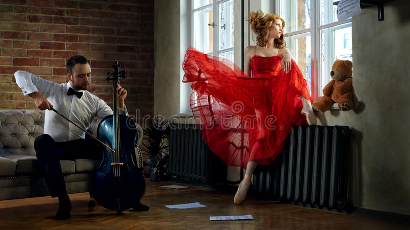 Handsome cellist visits the muse from fairytale. Caucasian handsome cellist visits the muse from fairytale in red dress stock images