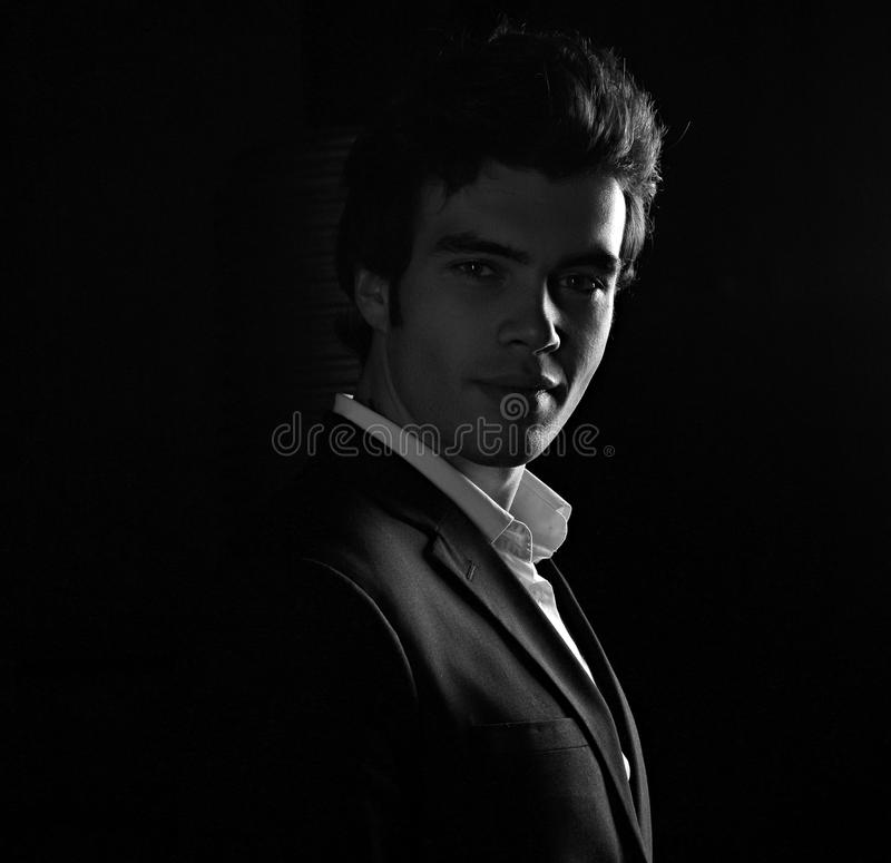 Handsome charismatic man looking with smiling on dark shadow dramatic light. Art. Black and white closeup portrait stock image
