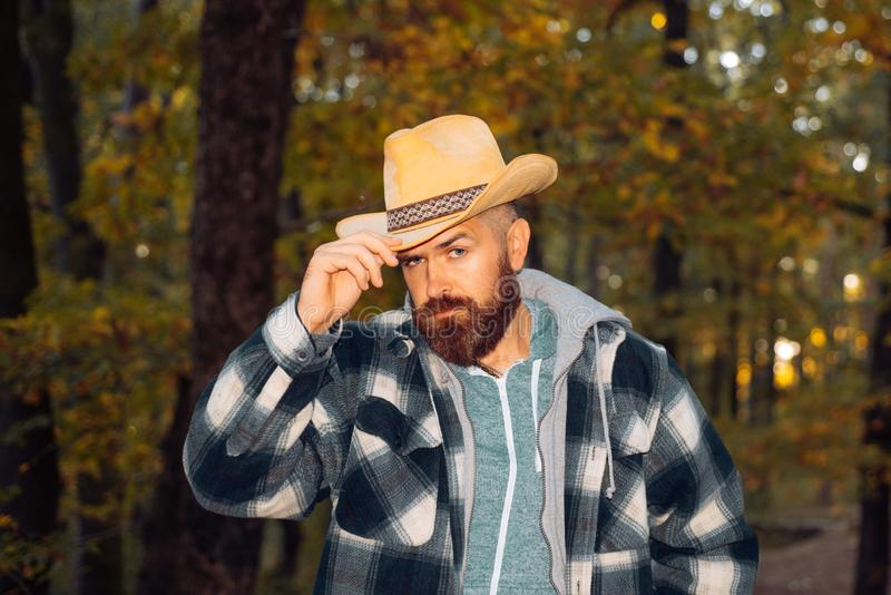 Handsome charming beard man in freezing cold in the autumn forest, wearing a cawboy hat. Traditions and reliability stock image