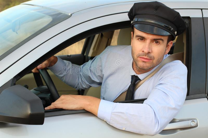 Handsome chauffeur looking at camera stock photography