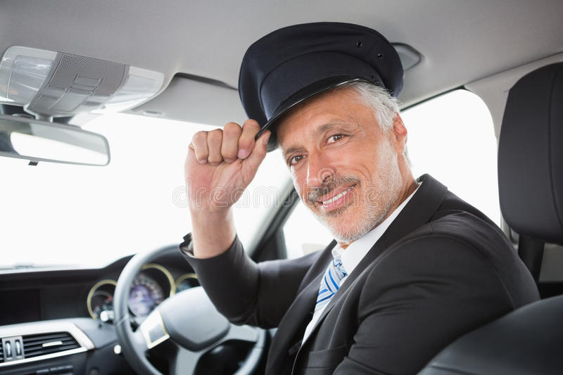 Handsome chauffeur smiling at camera. In the car stock photo