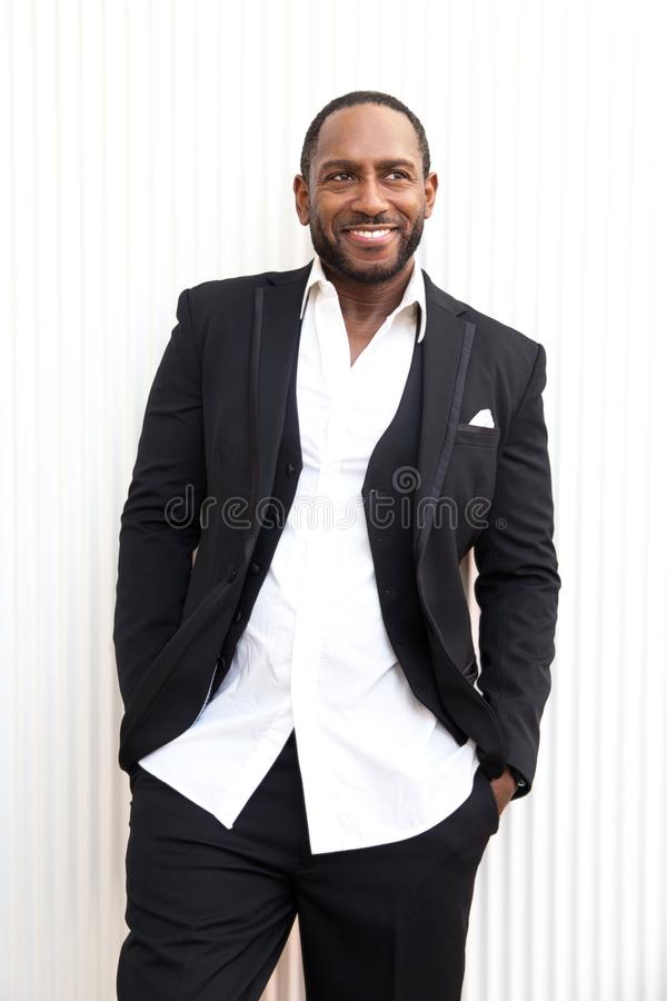 Handsome cheerful african american business man in classy black suit. stock photography
