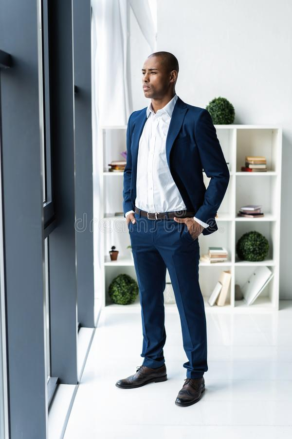 Handsome cheerful african american executive business man at the workspace office. stock photography