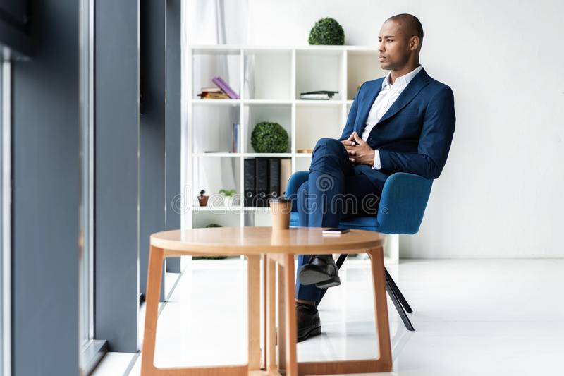 Handsome cheerful african american executive business man at the workspace office. royalty free stock image