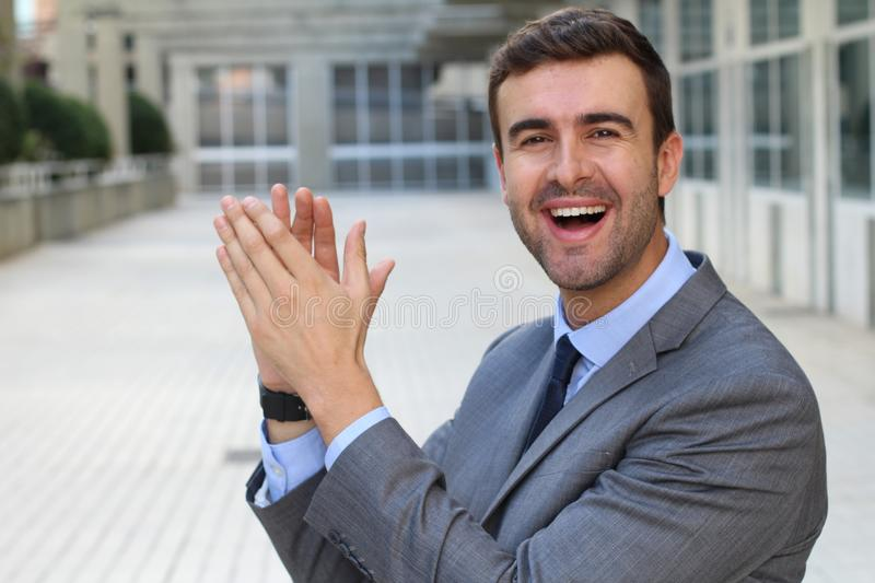 Handsome cheerful businessman clapping stock photos