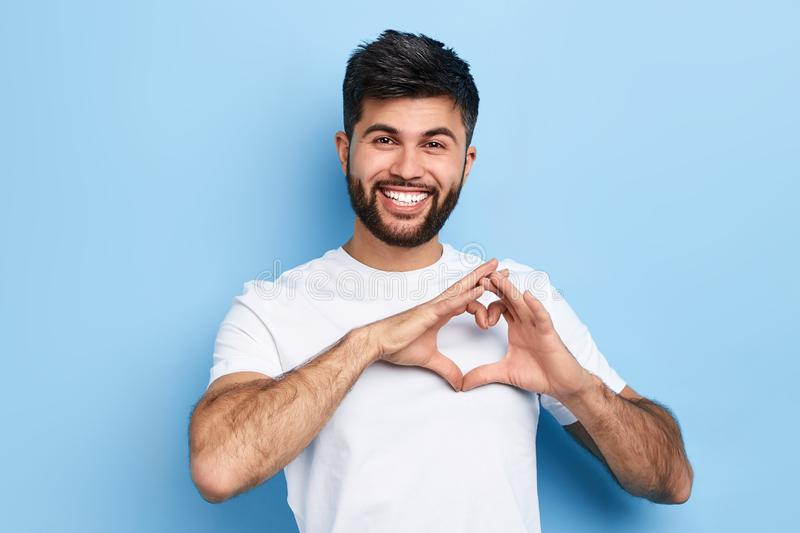 Handsome cheerful guy is making a heart shape symbol with his fingers. stock photography