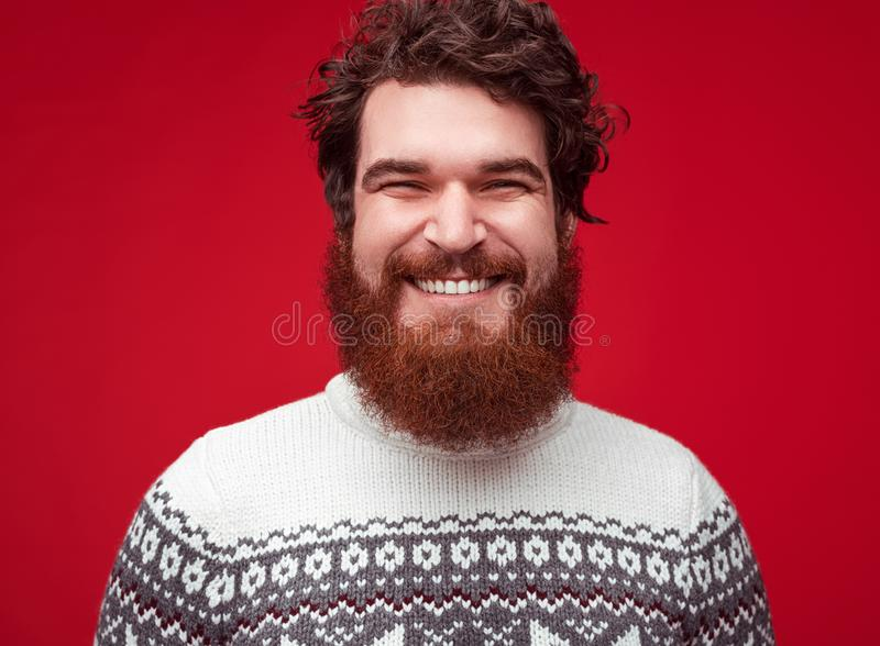 Handsome cheerful man unshaven looking to camera on red background stock photo