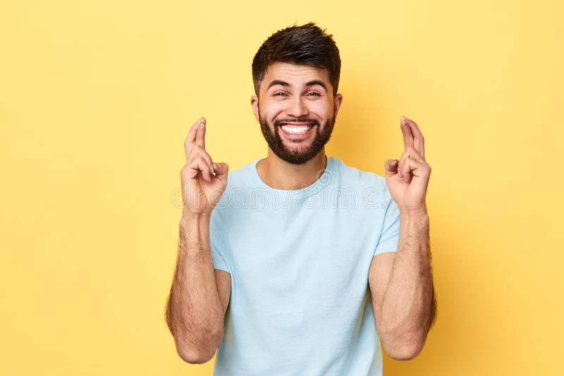 Handsome cheerful positive bearded man crossing his fingers royalty free stock photos
