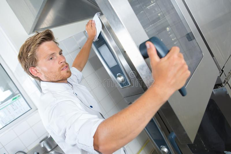 Handsome chef assistant cleaning kitchen with rag stock images