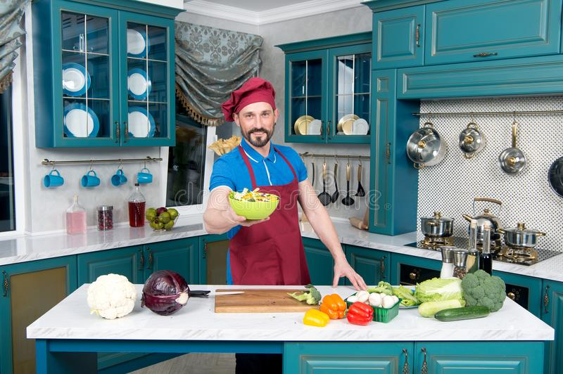 Handsome chef in hat loves cooking. Guy in blue polo and apron proposing green plate with salad. stock photo