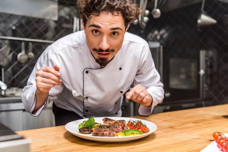 Handsome chef standing with fork above cooked vegetables. With meat stock photography