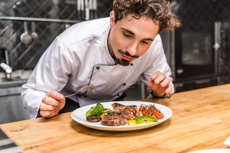 Handsome chef standing with fork above fried vegetables. With meat stock image
