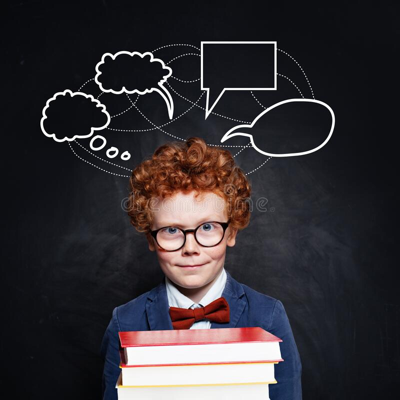 Handsome child with ginger curly hair holding books on blackboard background empty speech clouds bubbles royalty free stock photography