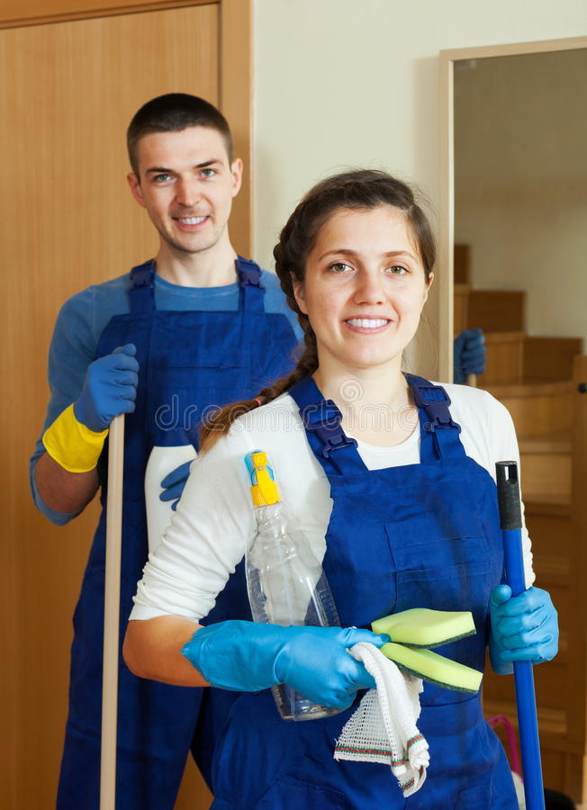 Handsome cleaners team at door stock photography