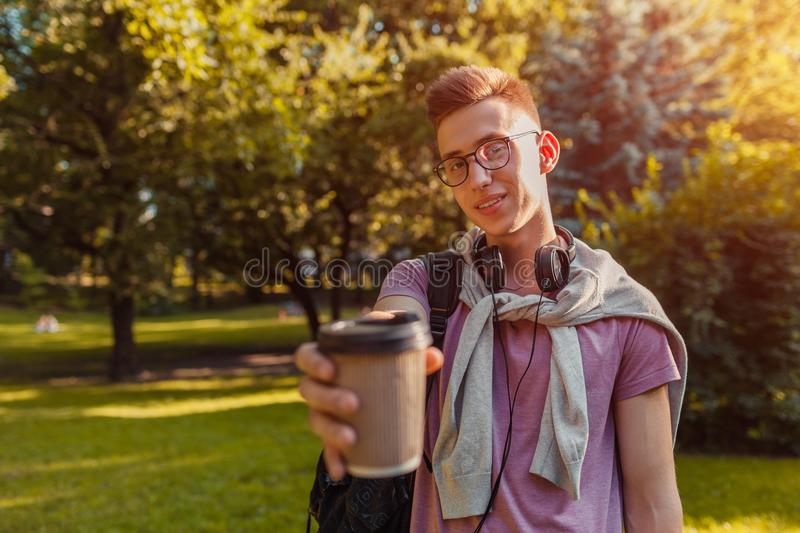 Handsome college guy chilling in spring campus park. Happy man student drinking coffee. Handsome college guy chilling in spring campus park. Happy man student royalty free stock photos