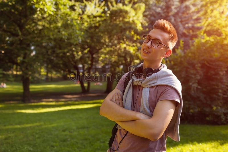 Handsome college guy chilling in spring campus park. Happy man student wears earphones and glasses. And looks at camera stock photos