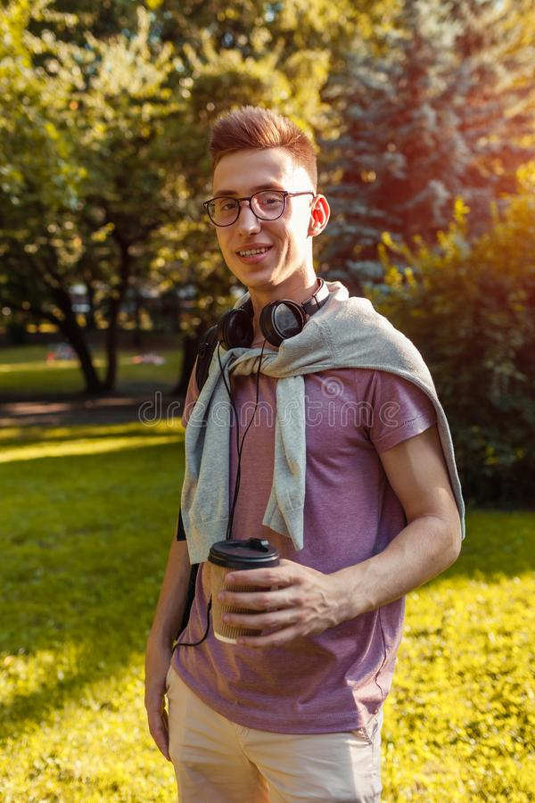Handsome college guy chilling in spring campus park. Happy man student wears earphones and glasses. And holds cup of coffee stock photos