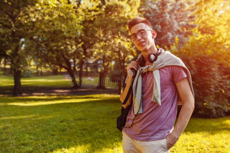 Handsome college guy chilling in spring campus park. Happy man student wears earphones and glasses. And looks at camera stock photography