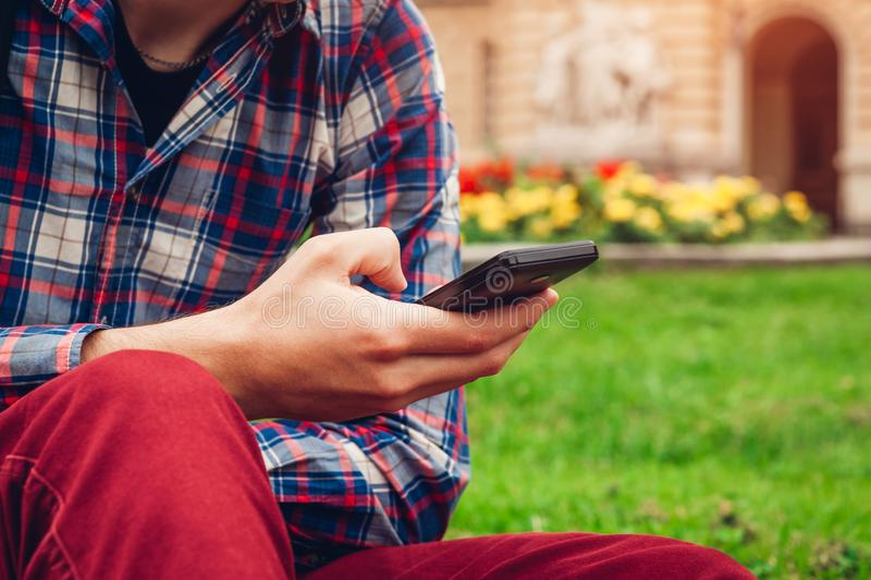 Handsome college man chilling in spring campus park. Happy guy student using smartphone. Handsome college man chilling in spring campus park. Happy guy student stock image