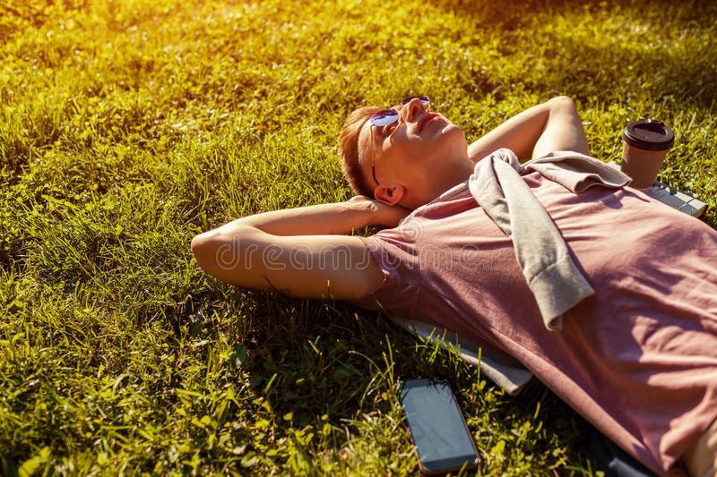 Handsome college man chilling in spring campus park. Happy guy student lying on grass with his phone and coffee beside. At sunset royalty free stock images