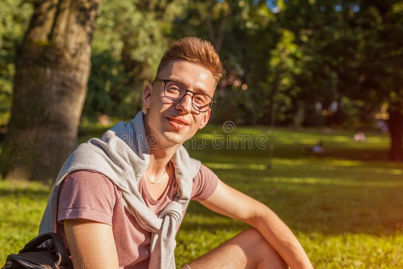 Handsome college man chilling in spring campus park. Happy guy student sitting on grass and looking at camera. At sunset stock photos