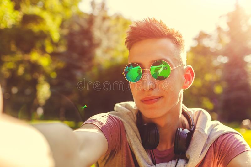 Handsome college man chilling in spring campus park. Happy guy student in sunglasses takes selfie. Handsome college man chilling in spring campus park. Happy guy royalty free stock photos