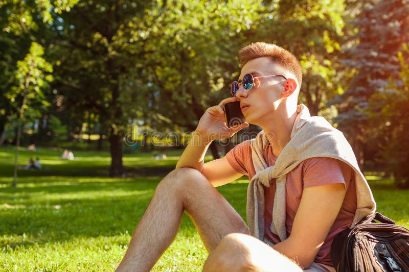Handsome college man hanging in smartphone in campus park. Happy guy student learning outdoors sitting on grass. In spring royalty free stock photography