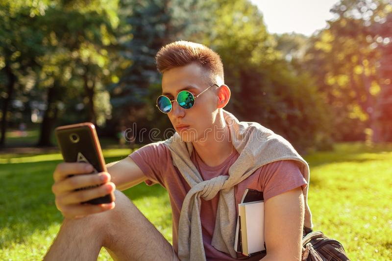Handsome college man hanging in smartphone in campus park. Happy guy student learning outdoors sitting on grass. In spring stock photography