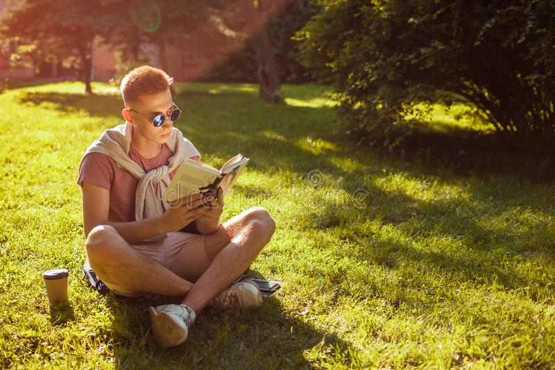 Handsome college man reading a book and drinking coffee in campus park. Happy guy student learning sitting on grass. Handsome college man reading a book and royalty free stock photography