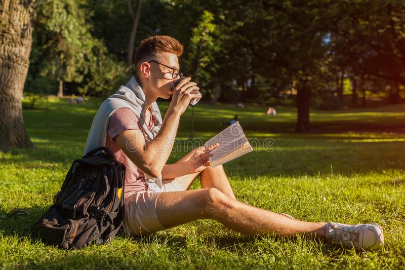Handsome college man reading a book and drinking coffee in campus park. Happy guy student learning sitting on grass. Handsome college man reading a book and stock photography