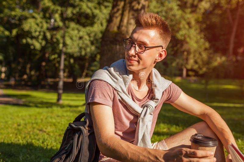 Handsome college man reading a book and drinking coffee in campus park. Happy guy student learning sitting on grass. Handsome college man reading a book and royalty free stock photos
