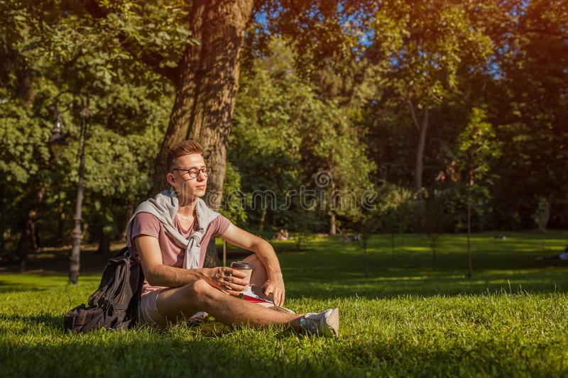 Handsome college man reading a book and drinking coffee in campus park. Serious guy student learning sitting on grass. Handsome college man reading a book and royalty free stock photography