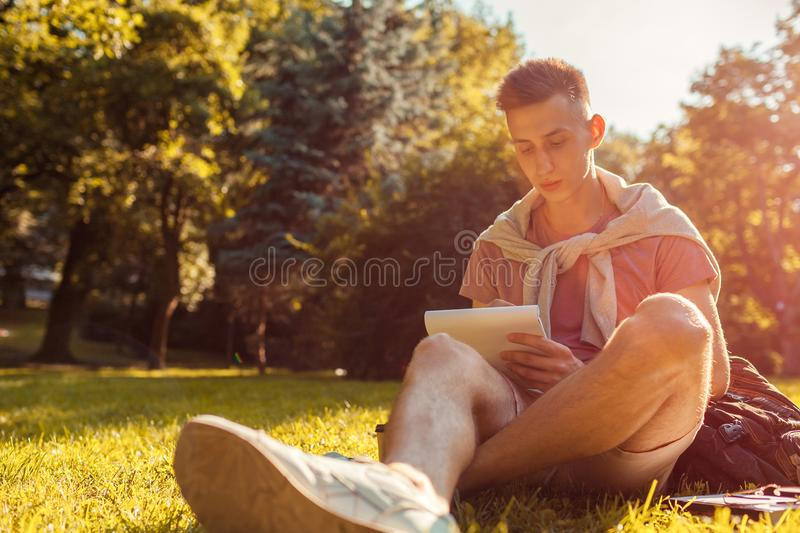 Handsome college man writing notes in copybook in campus park. Happy guy student learning outdoors sitting on grass. In spring. Education stock images